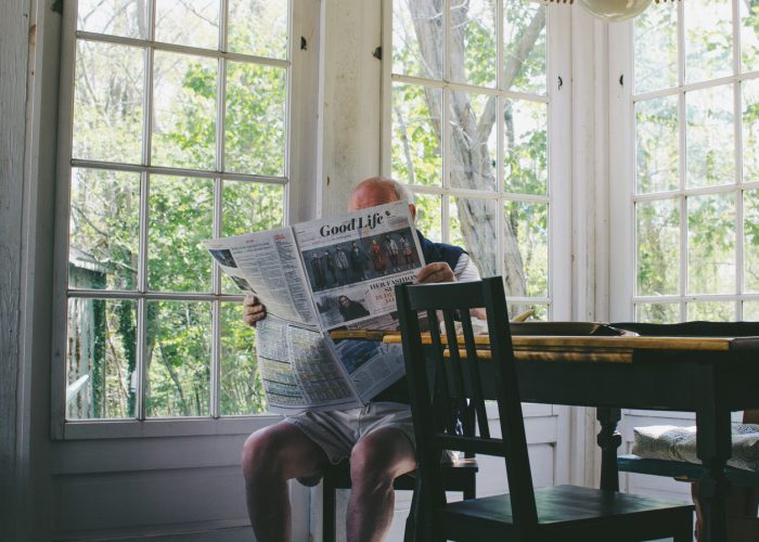 man sat at home reading newspaper