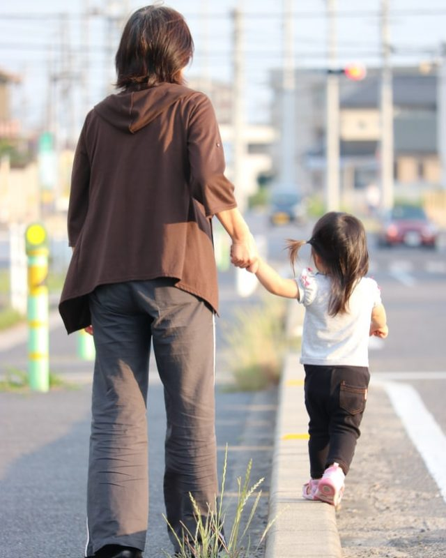 child walking holding parent's handf